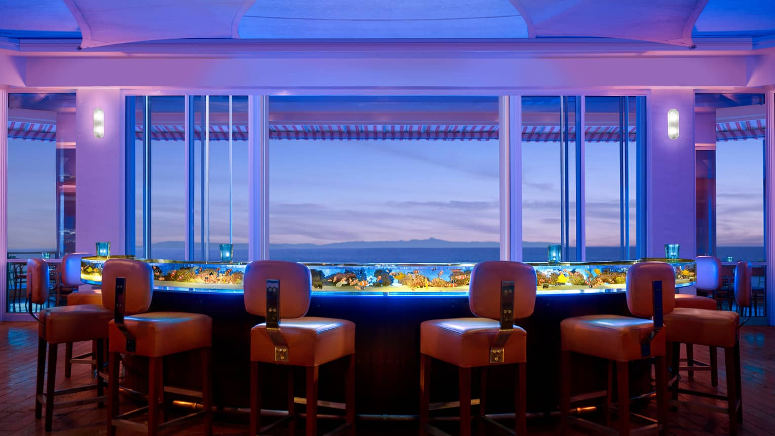 Orange stool around glowing Coral Reef glass bar filled with water, tropical fish