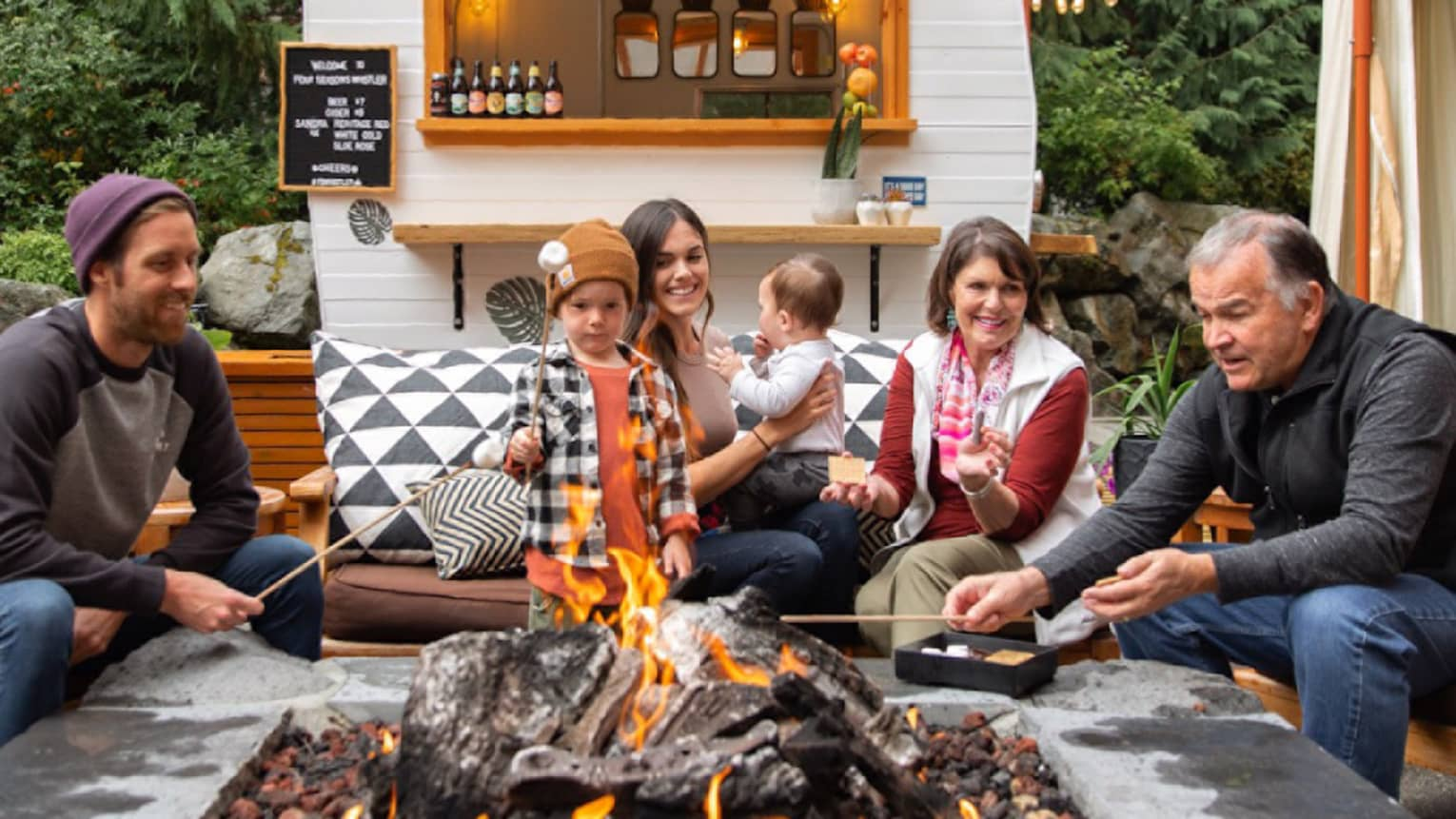 Family roasts marshmallows around outdoor fire pit by bar cart