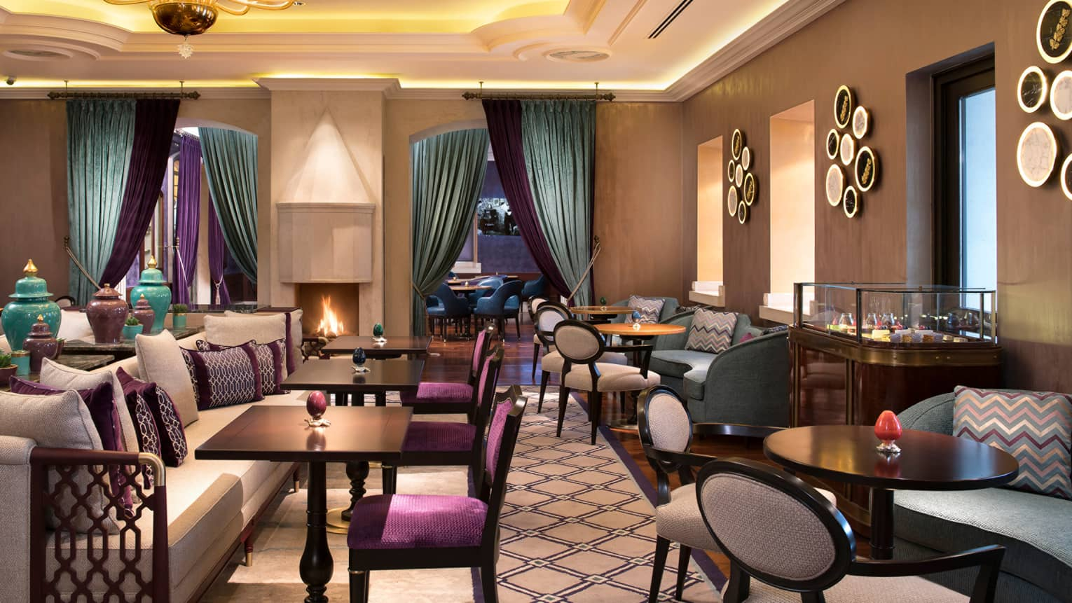 Restaurant featuring a chandelier, carpeting, dark wood tables, light purple upholstered chairs, turquoise drapes