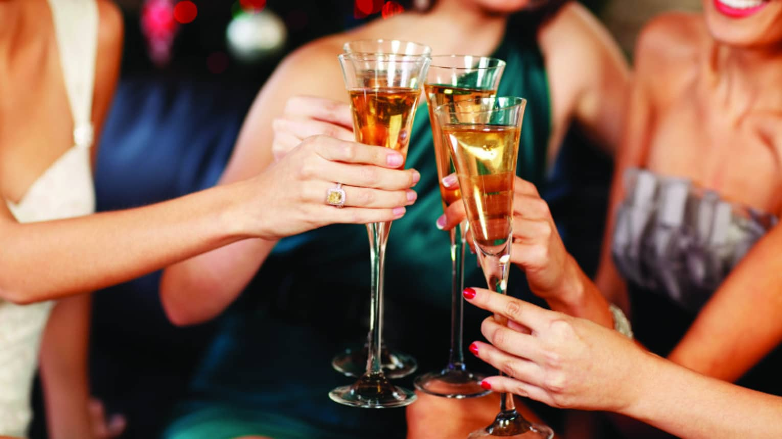Close-up of women in evening gowns toasting with glasses of Champagne