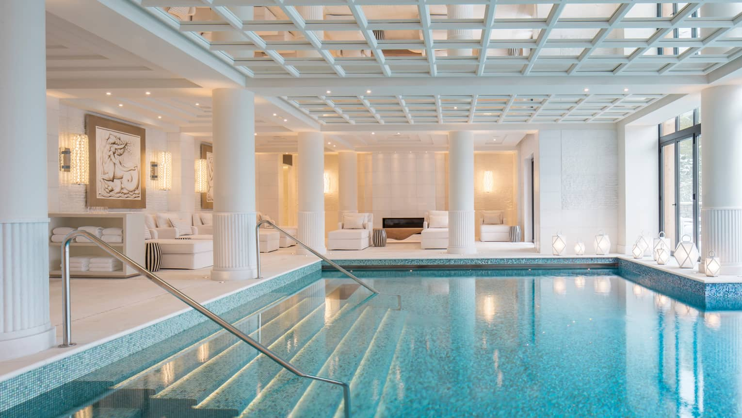 Indoor swimming pool under white beams, pillars, lounge chairs on deck