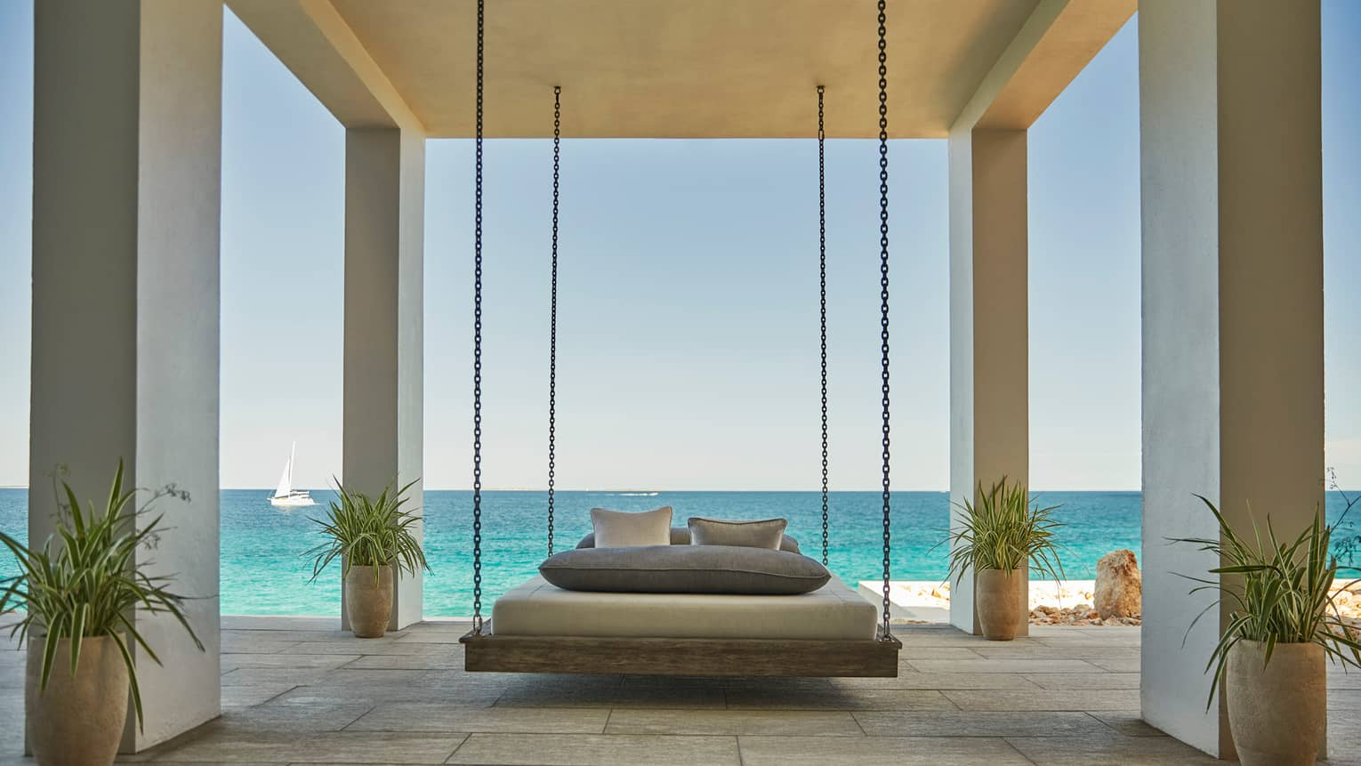 Patio bed hangs by chains from white ceiling in outdoor room with tropical potted plants, ocean view