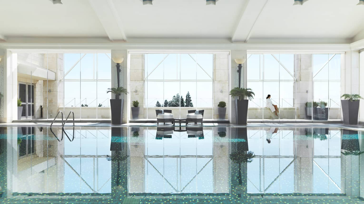 Indoor swimming pool reflecting three tall windows, woman in white bathrobe sits on ledge