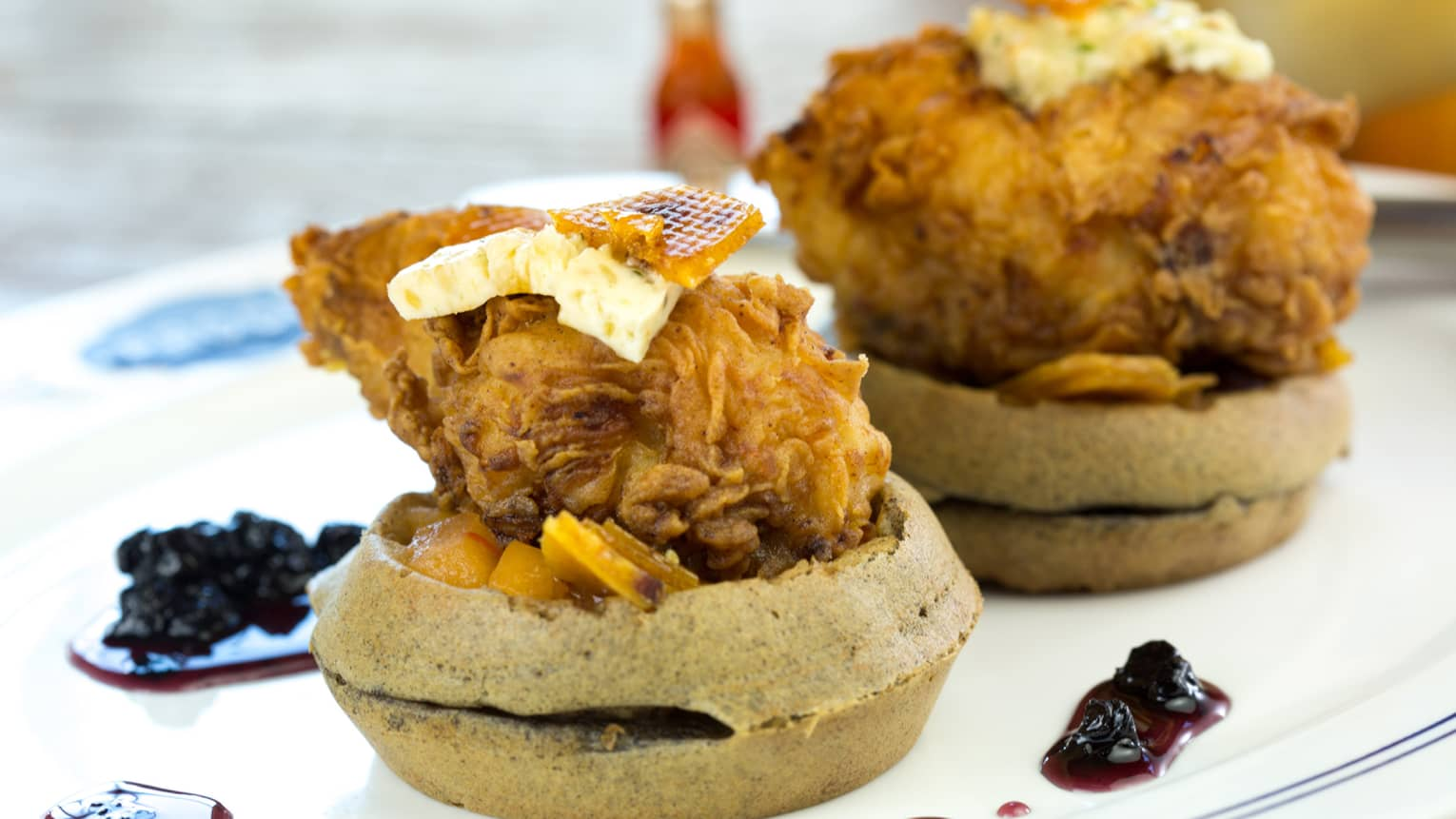 Two stacks of round waffles topped with fried chicken, butter, honey comb