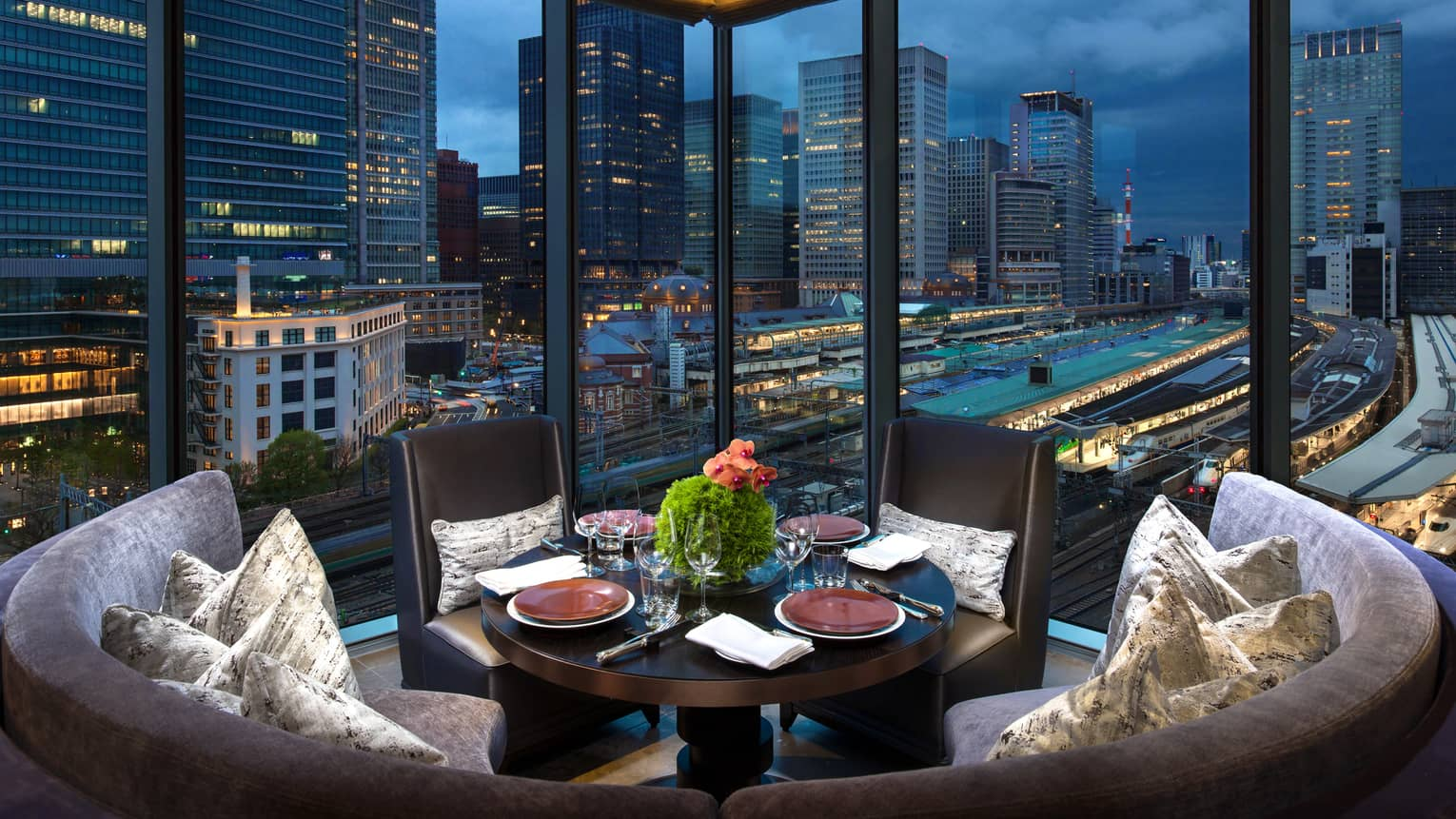 Circular sofa, velvet pillows, cocktail table by floor-to-ceiling window at Motif Restaurant
