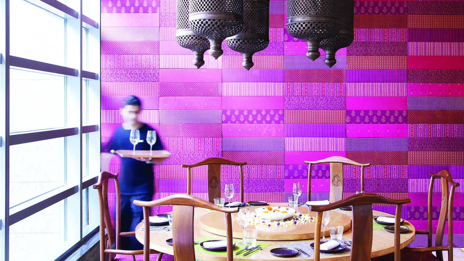 Waiter holds tray with wine glasses by large round dining table in front of purple textile wall