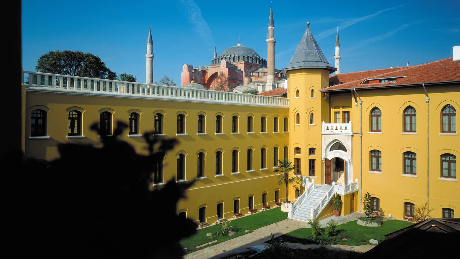 St. Sophia dome behind bright yellow walls of Four Seasons Hotel Istanbul Sultanahmet building