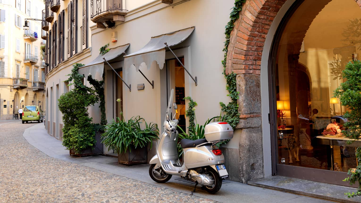 Silver moped motorcycle parked in front of brick archway in Milan's shopping district