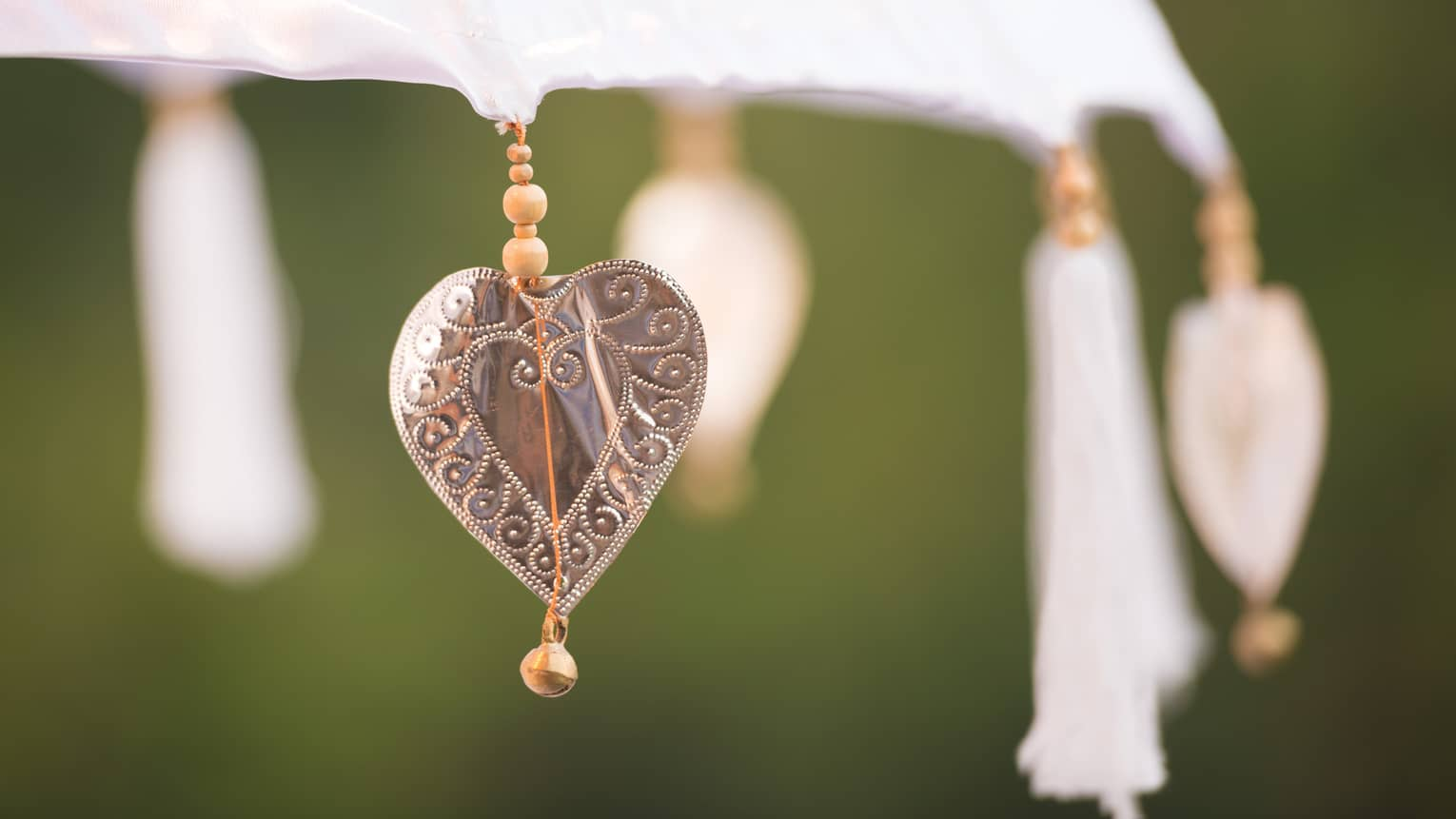 Close up of heart shaped charm, tassels