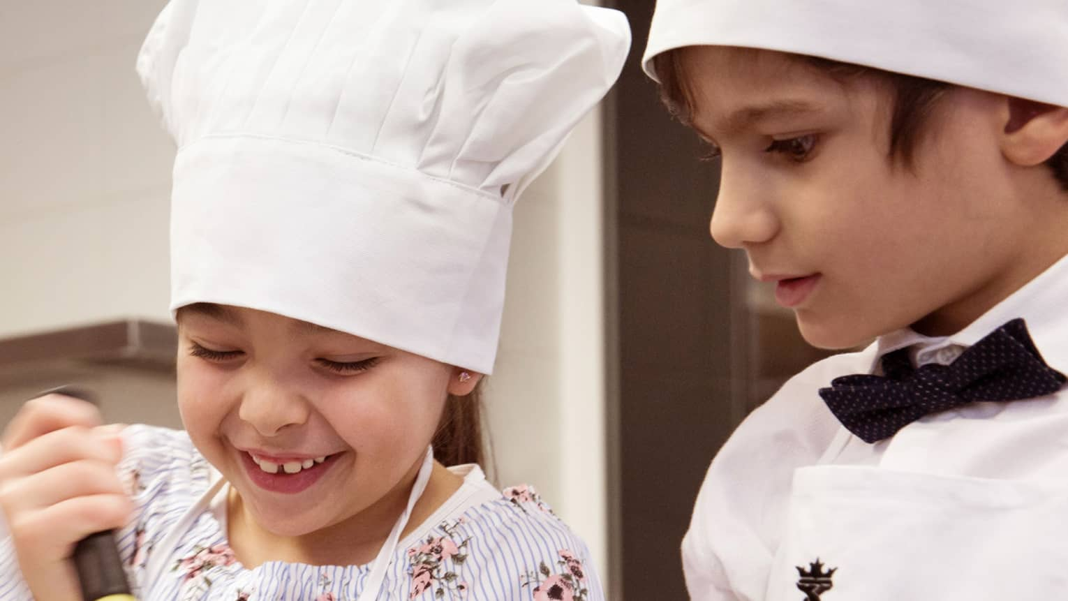 Girl and boy in chef hats; girl stirring with whisk, boy watching