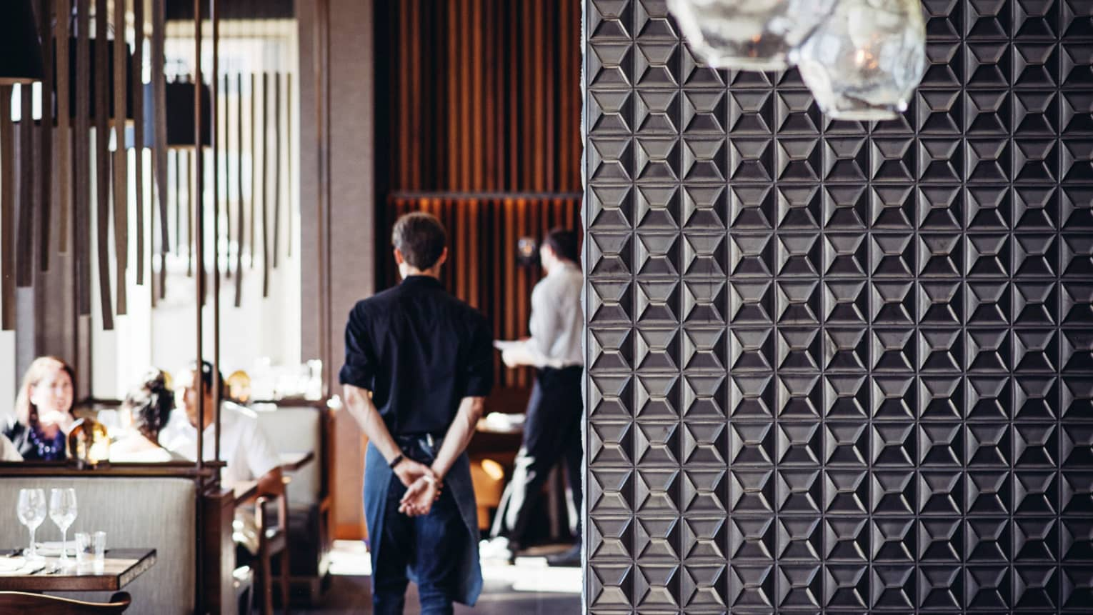 Server walks with hands behind back past dining tables, beyond decorative metal wall