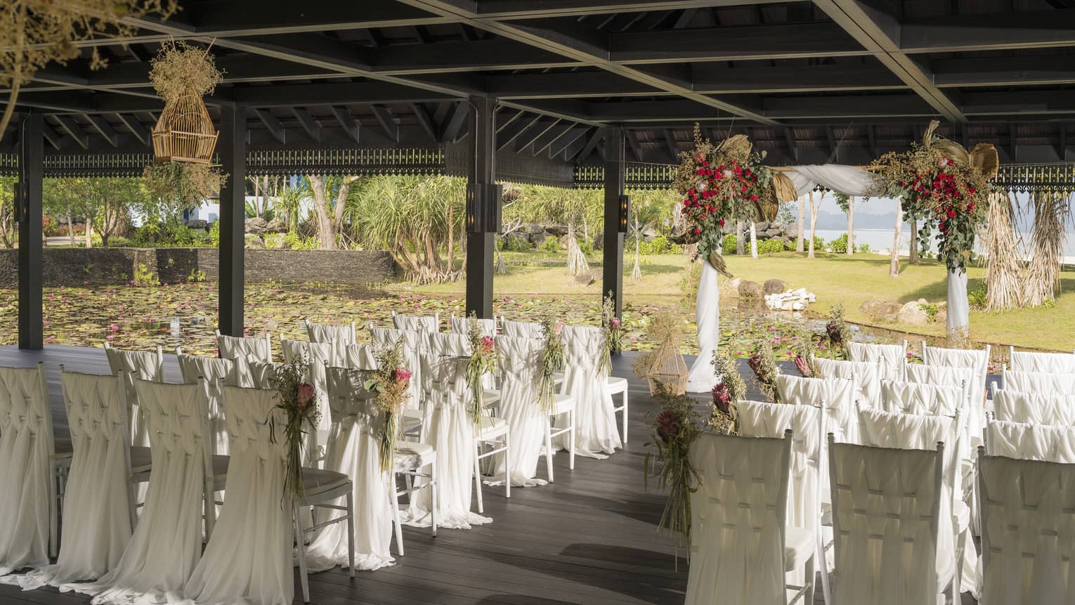 Outdoor wedding reception under pavilion, rows of chairs with white linens
