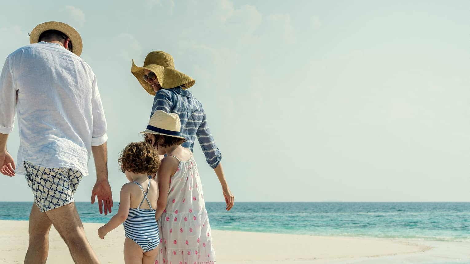 Family wearing swimsuits, sundresses and sun hats walk along white sand beach