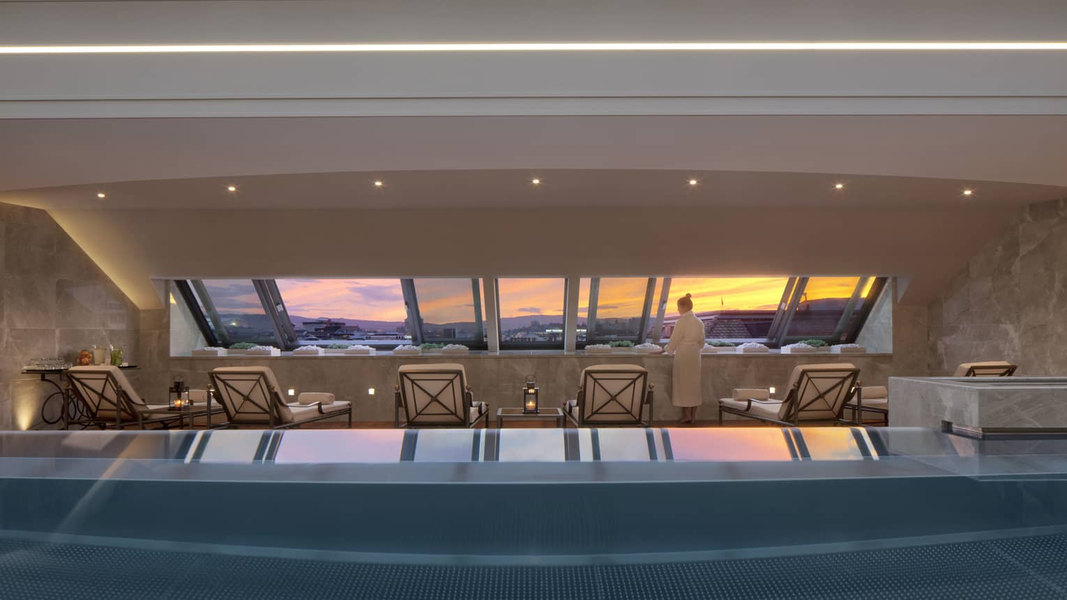 Woman in robe stands on deck beside blue indoor swimming pool, lounge chairs, looking at sunset through window