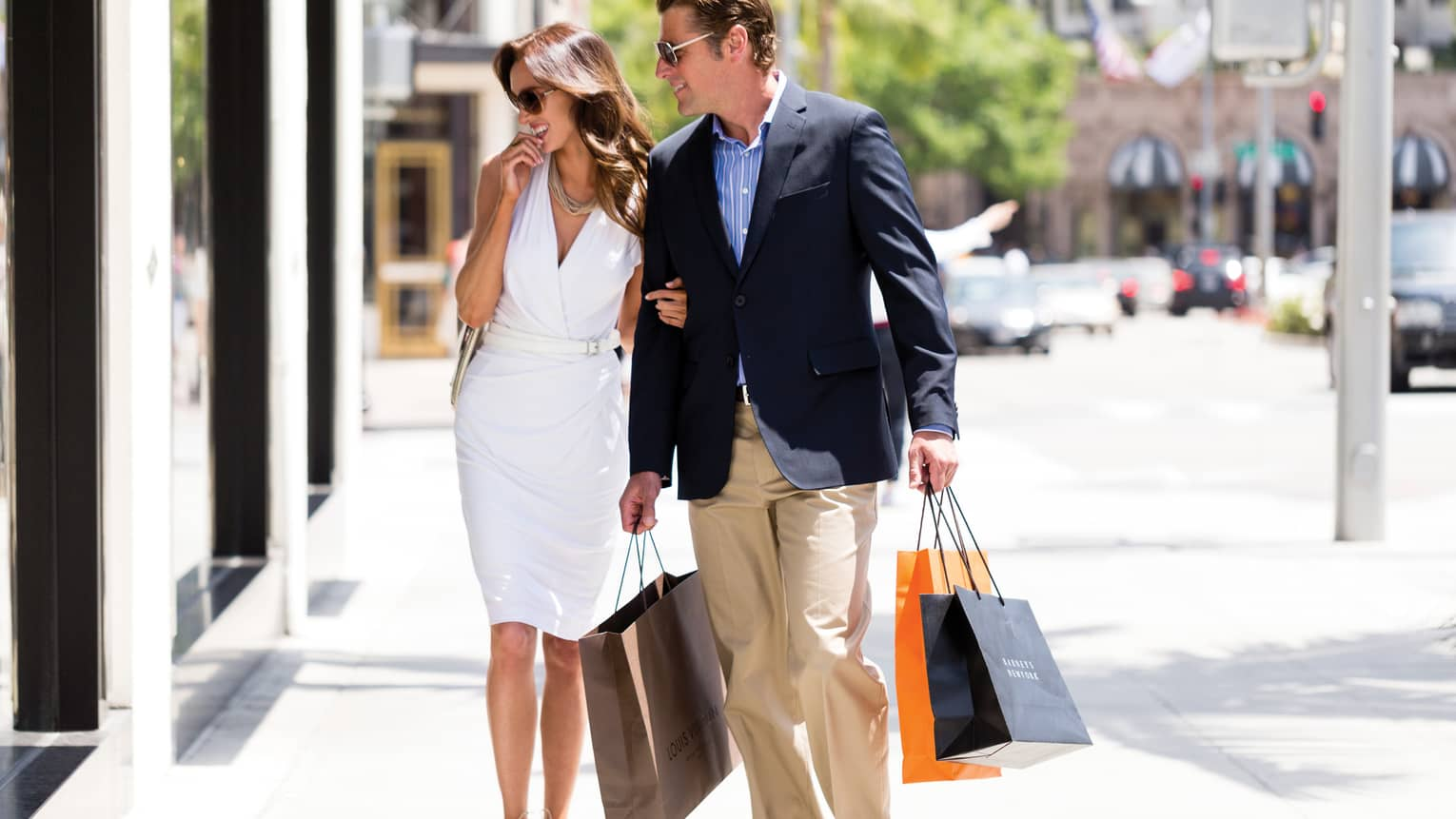 Man and woman carry shopping bags down sunny Rodeo Drive