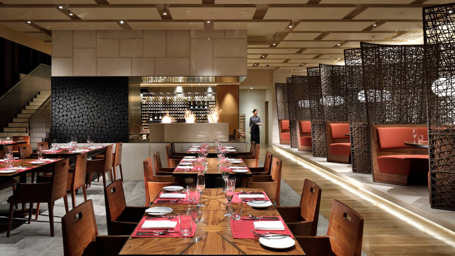 Modern dining room with rows of wood tables, large wine cellar, booths by black woven screens