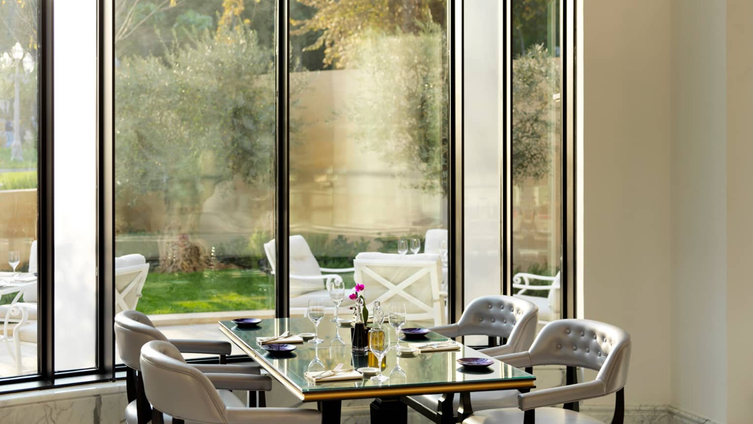 Zafferano restaurant with tall sunny window with dining table and four chairs