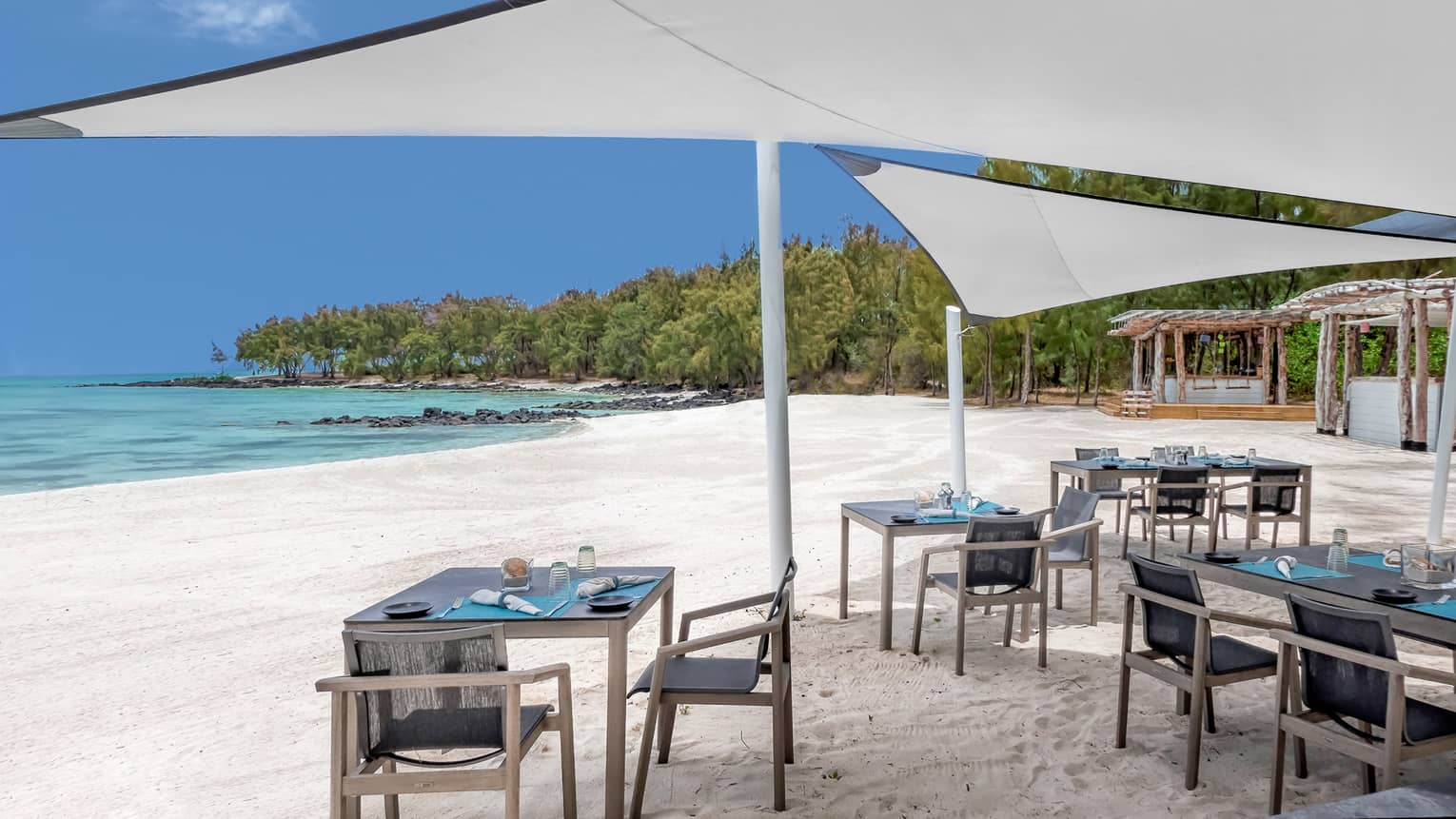 Small dining tables under white umbrella canopies on white sand beach near ocean