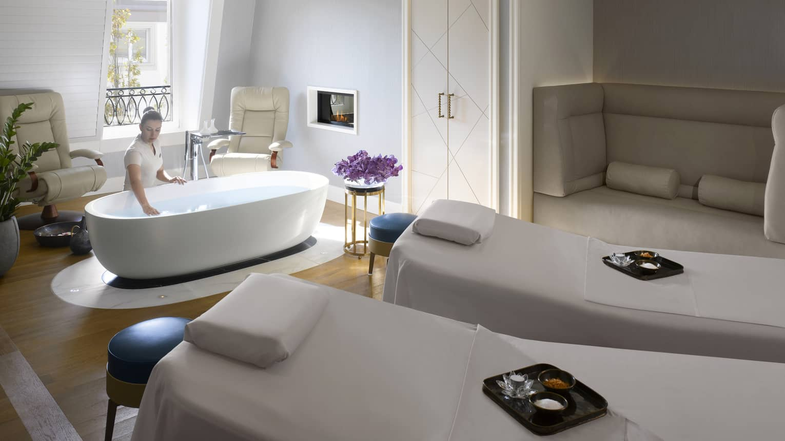 Two white spa beds side-by-side with yellow sashes, trays with salts and oils, woman makes bath
