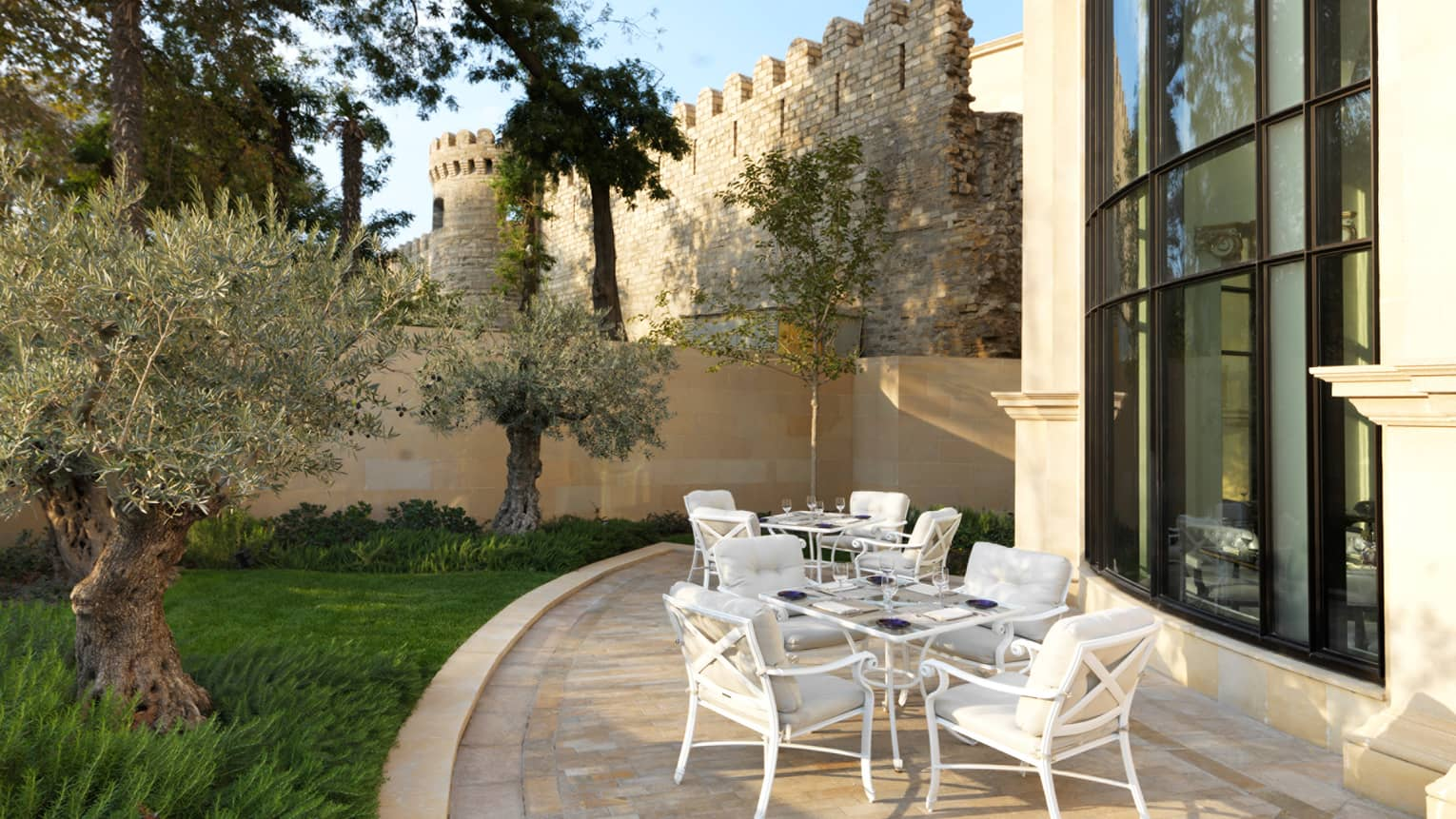 Zafferano curved patio with white iron tables and chairs, historic castle-like wall in background
