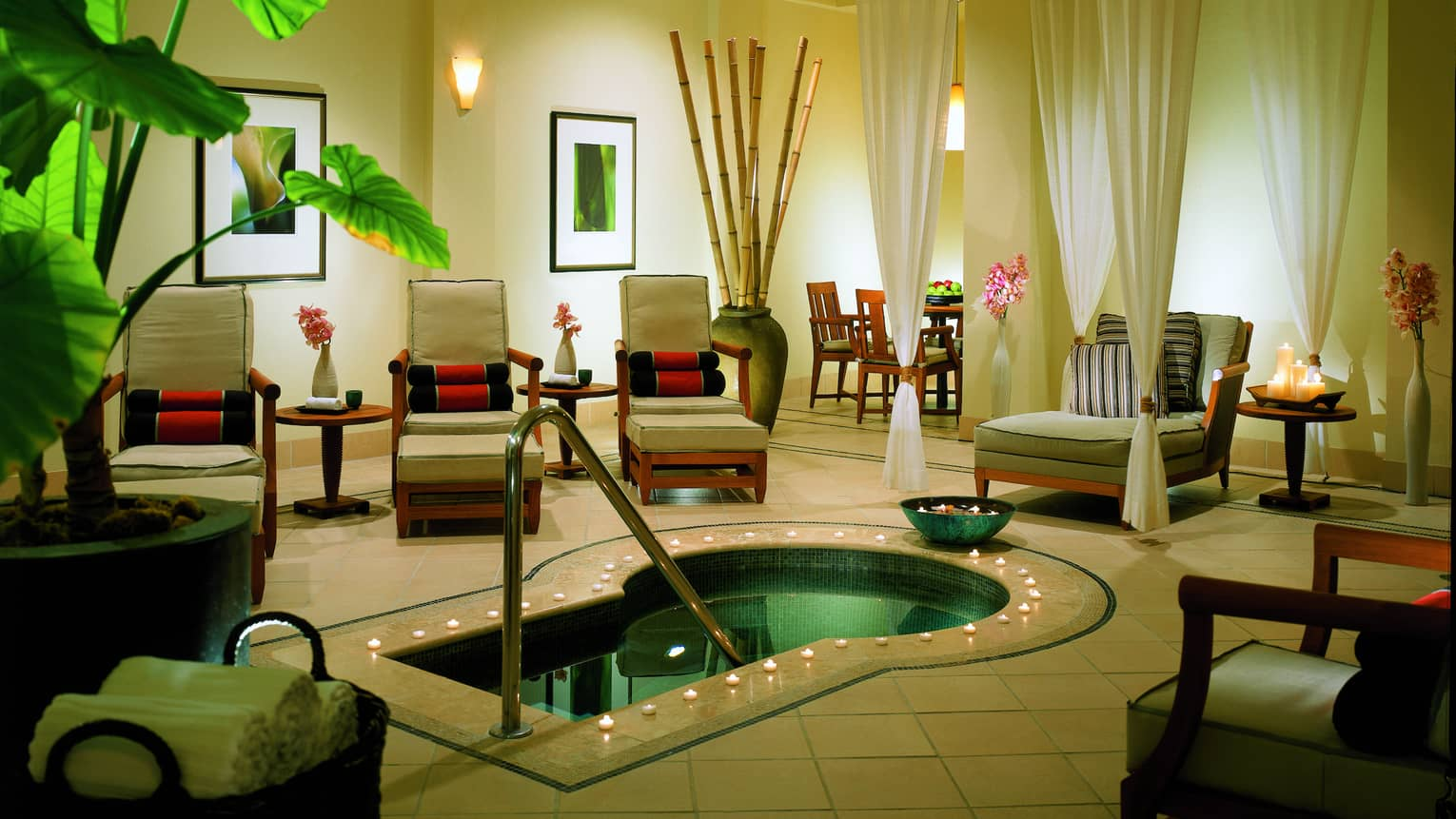 Tealight candles around small pool in spa room with lounge chairs, white curtains, plants