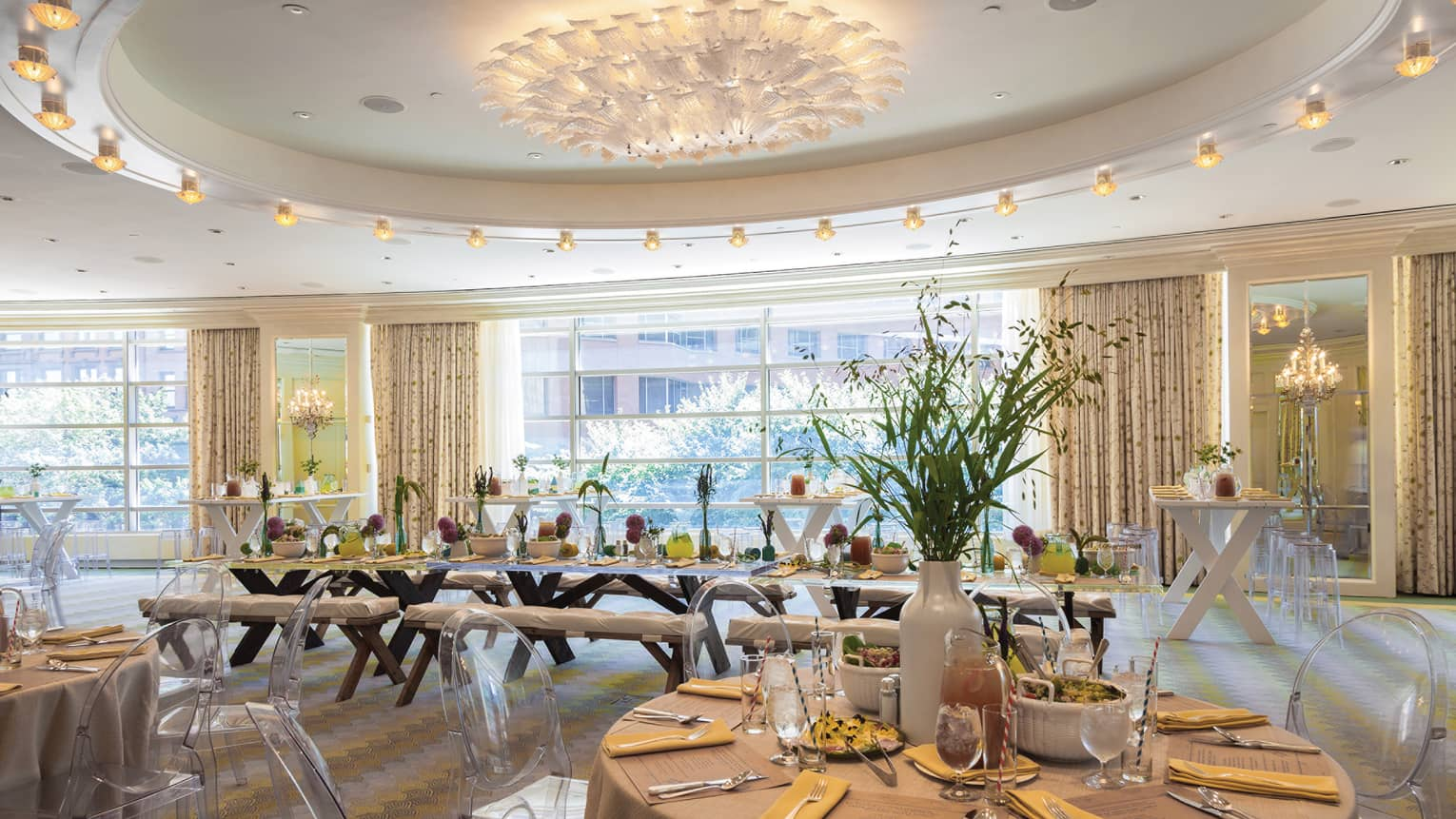 A bright room with circular tables has menus at each place setting in preparation for a meal