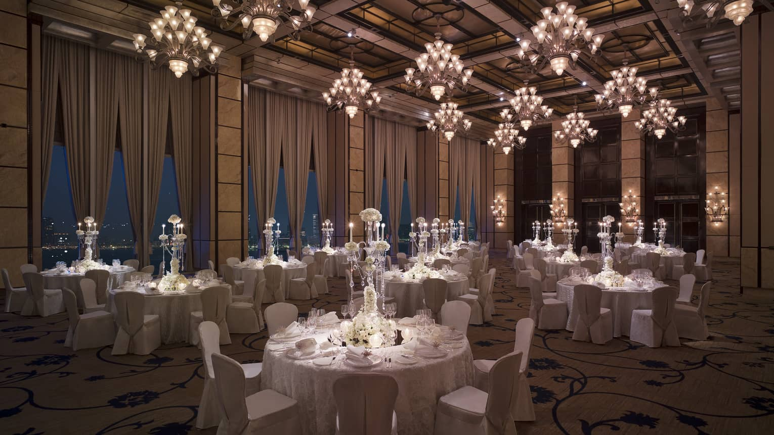 Wedding reception room with round banquet dining tables under small crystal chandeliers