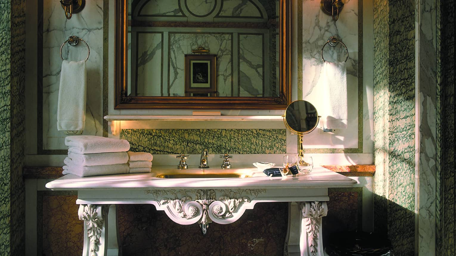 Elegant marble bathroom with decorative white vanity, folded white towels, mirror
