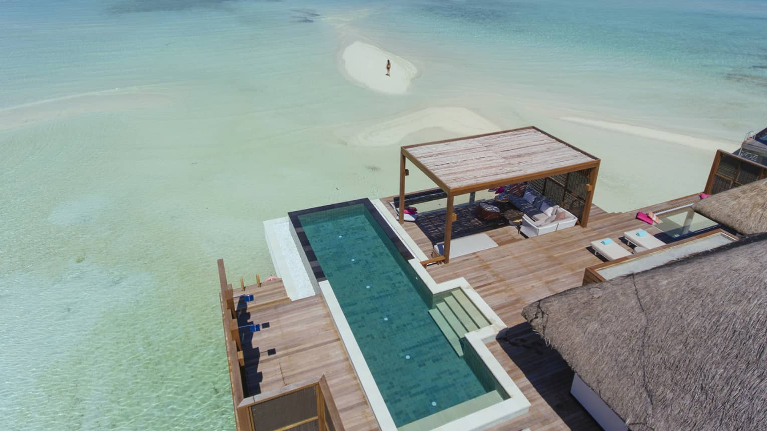 Aerial view of overwater bungalow with swimming pool, woman standing on sandbar in lagoon
