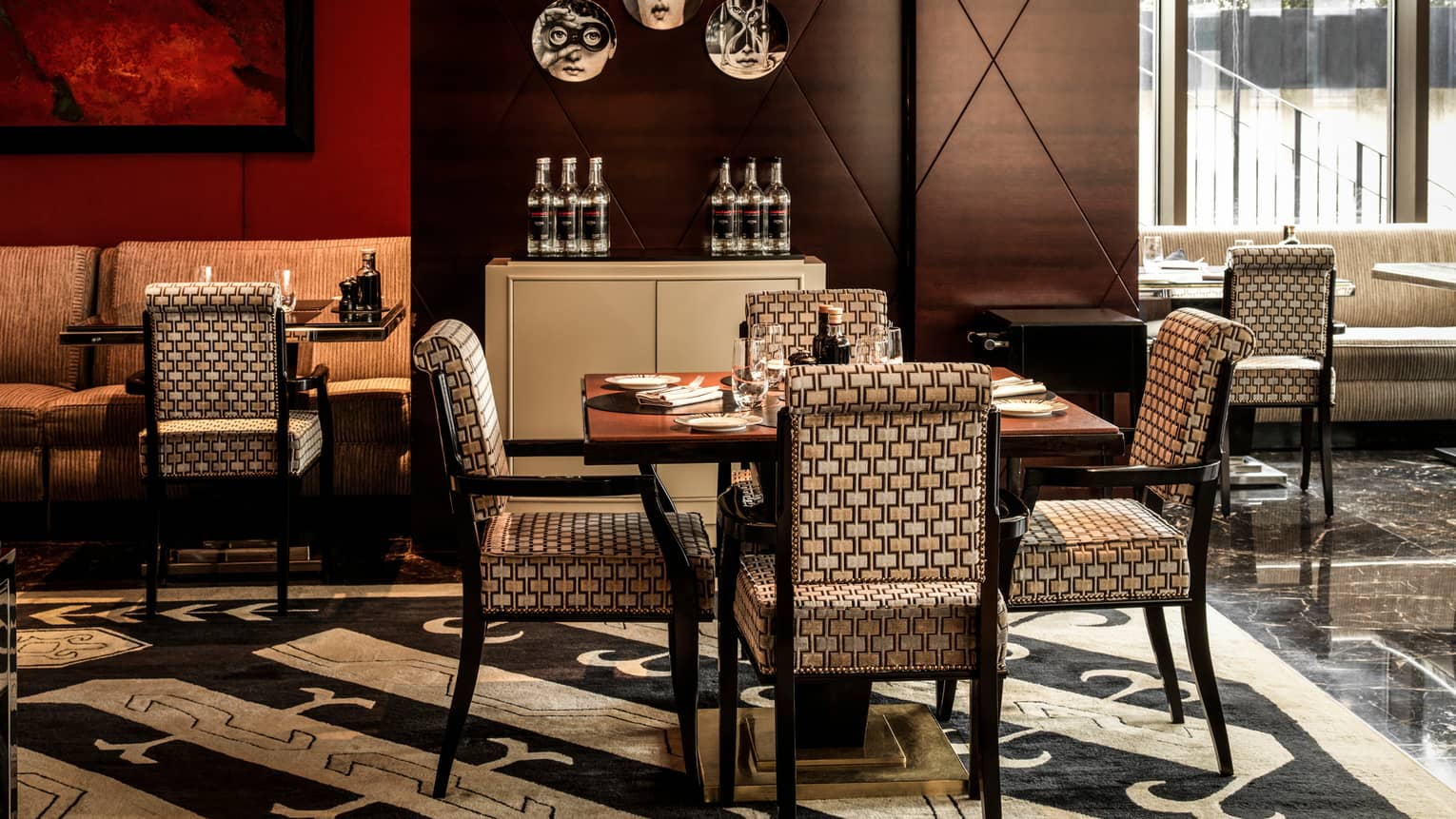Amaranto restaurant dining table, upholstered chairs, red walls, black-and-white carpets