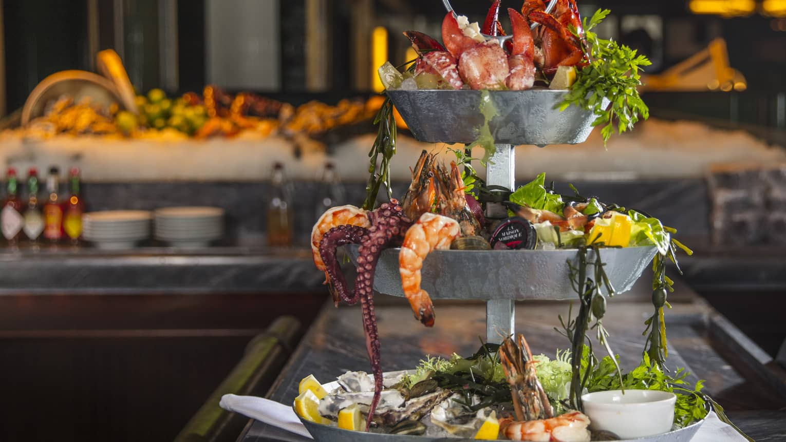 Three-tiered silver Grand Seafood Tower with shrimp, octopus, lobster claws, fresh lemon