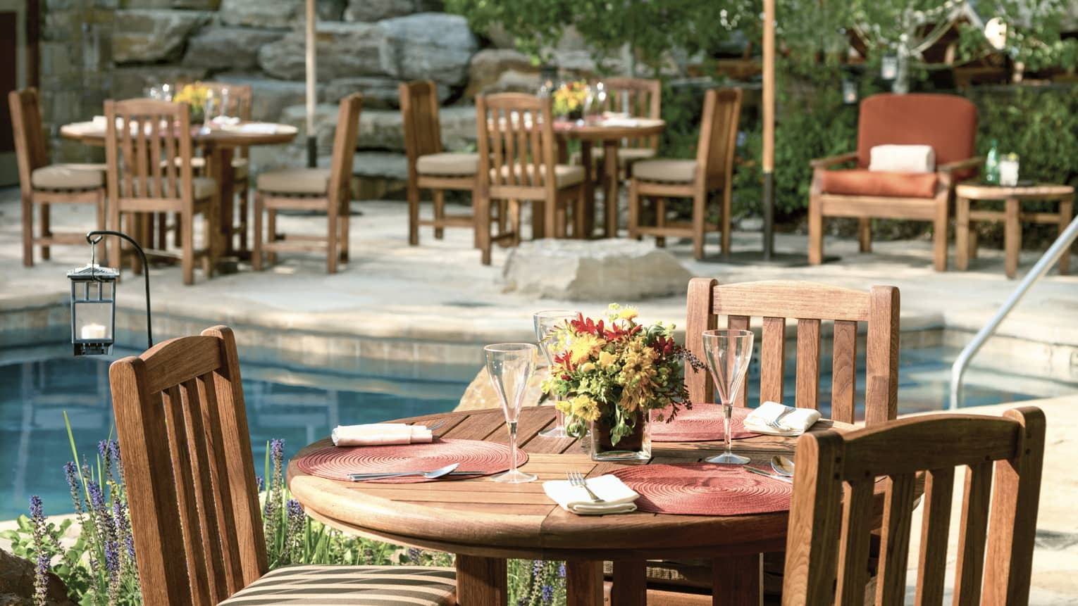 Poolside cafe table-setting with patio umbrellas and fresh-cut flowers.