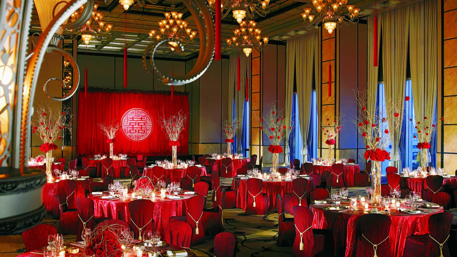 Elegant wedding banquet hall with red table linens and flower centrepieces, high ceilings, chandeliers