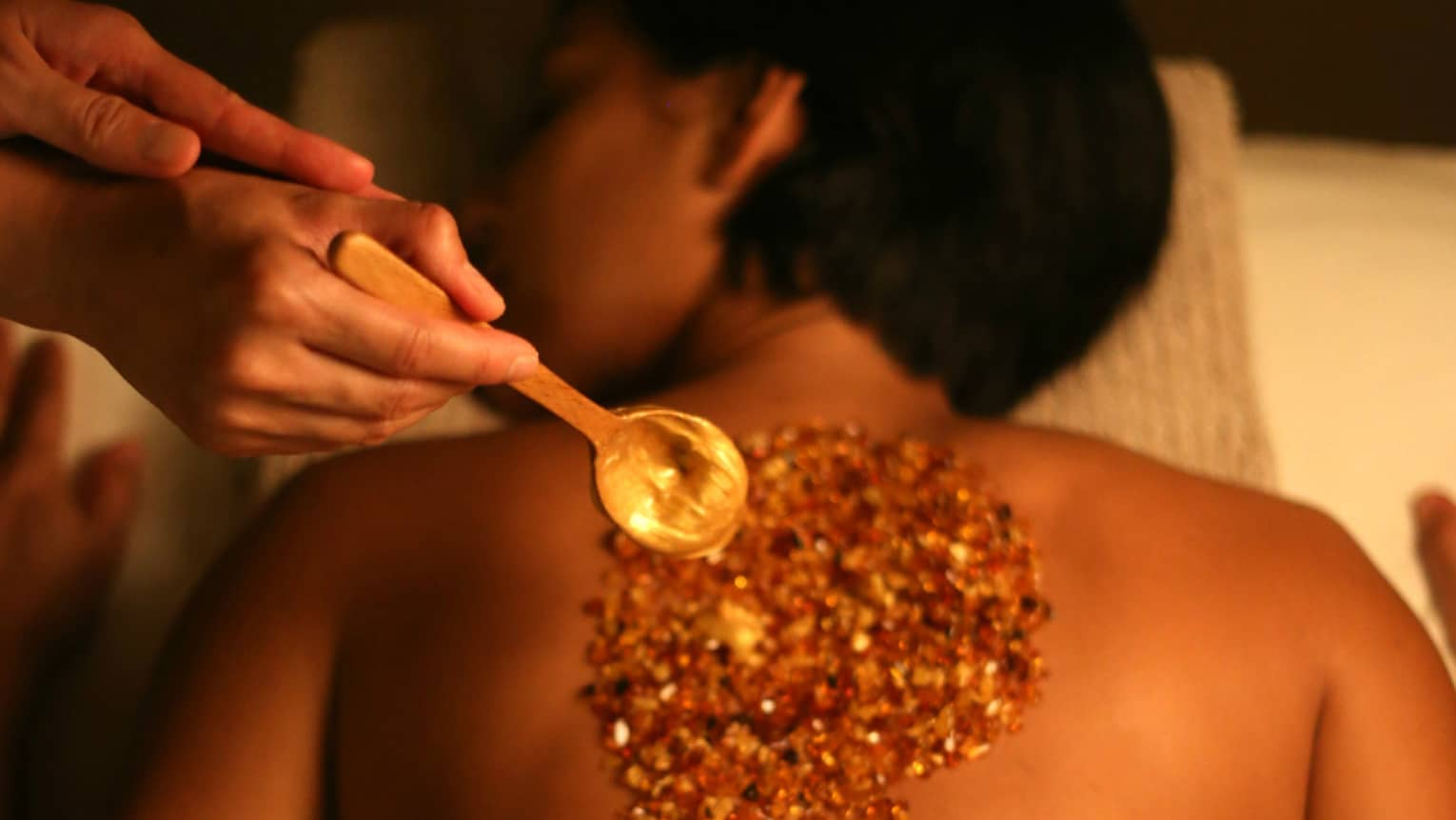 Spa staff holds wood spoon over woman's back covered with crystal spa rub