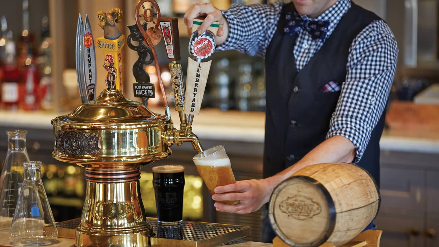 Bartender in vest, uniform pours beer into pint glass from taps at bar