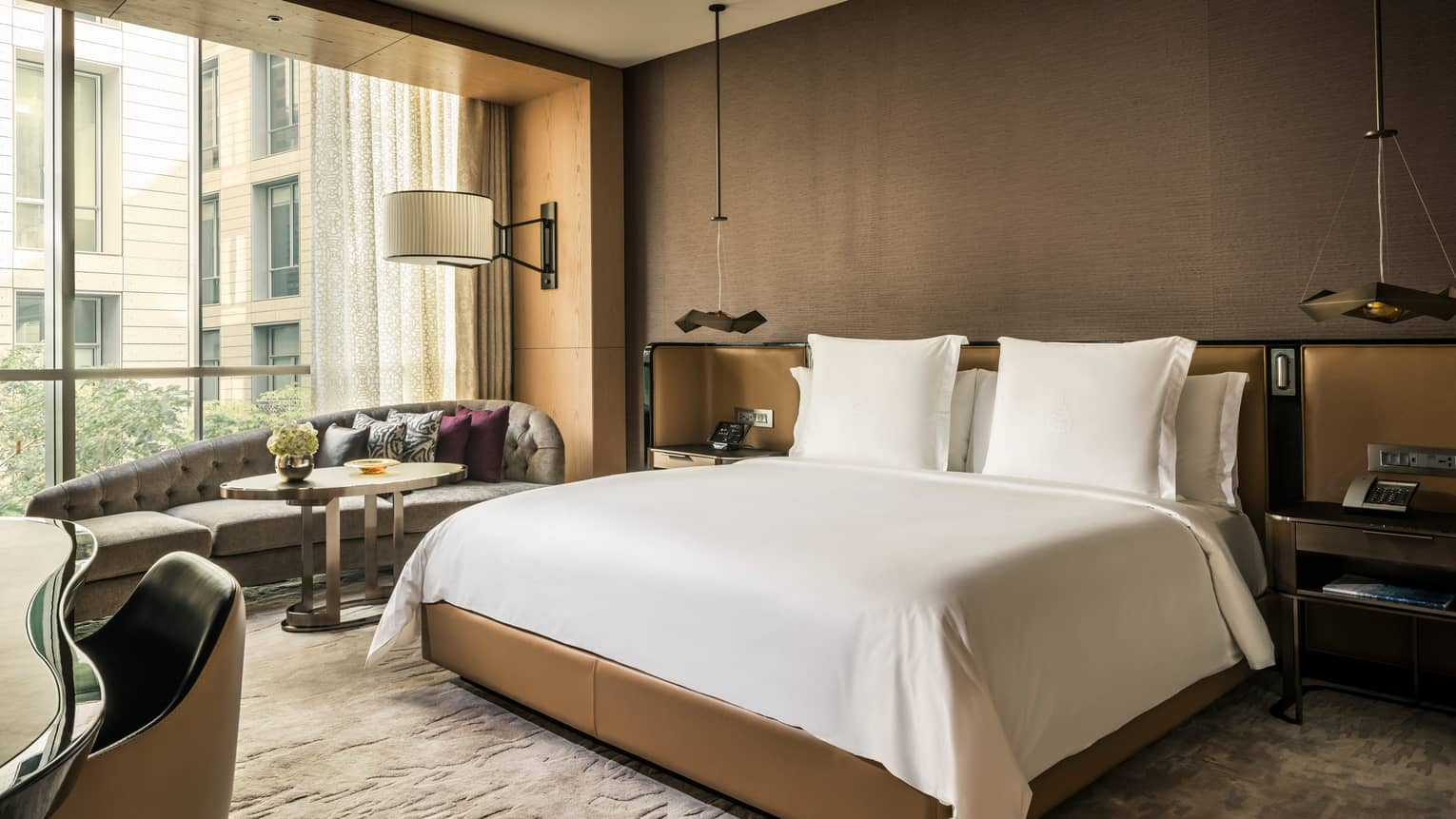 Deluxe Room hotel bed with padded headboard and nightstands, chaise under sunny window