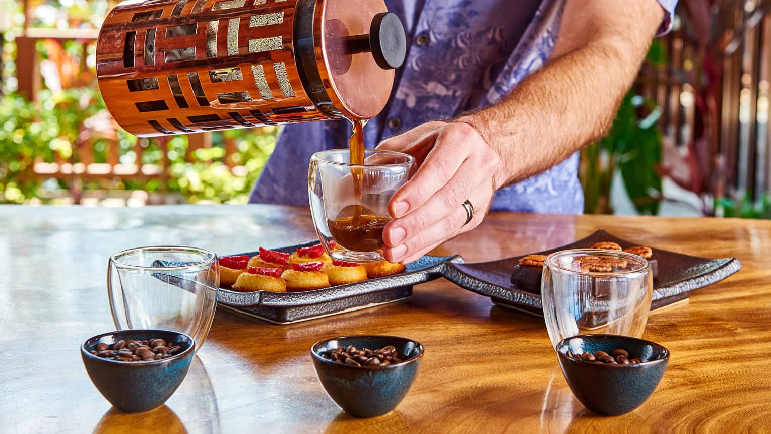 Server pouring coffee from carafe into tasting mugs, desserts on trays, bowls with beans