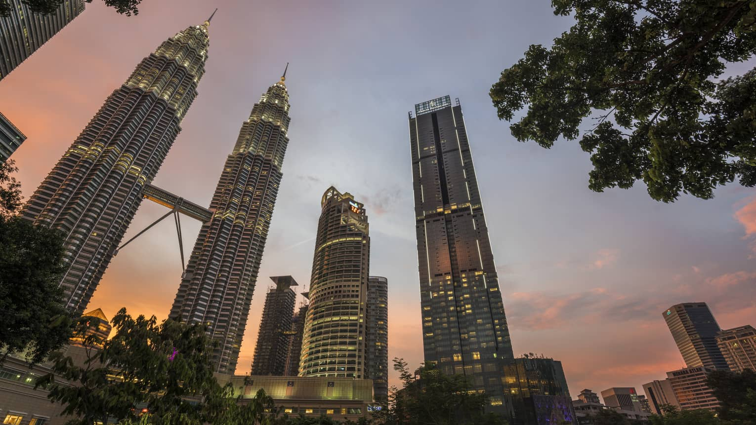 Four Seasons Hotel Kuala Lumpur against the sunset with the city skyline