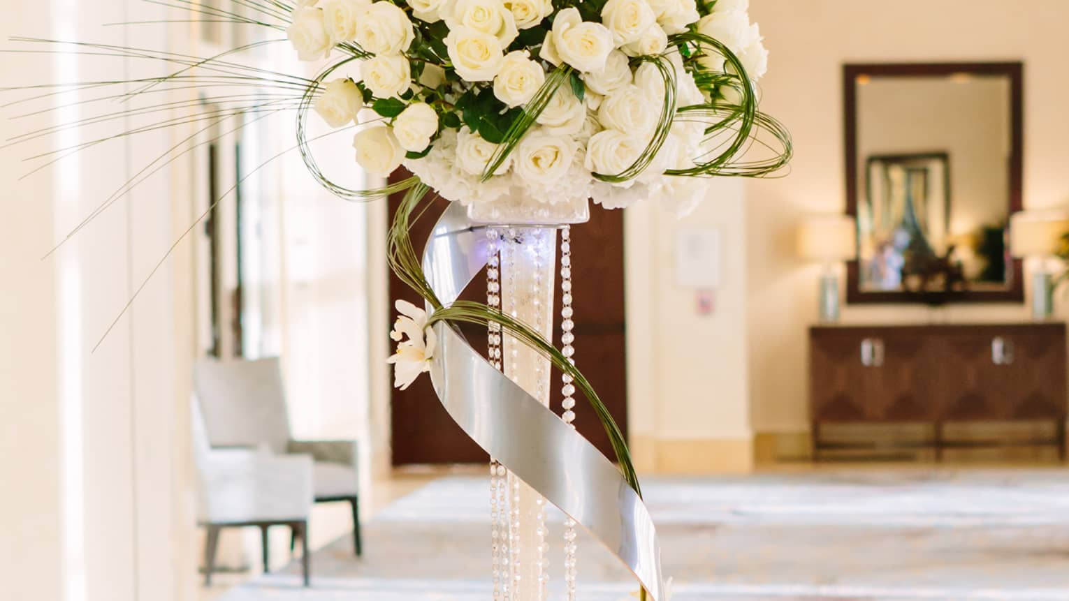 Wedding accent table with rows of name cards, tall white flower arrangement with ribbon