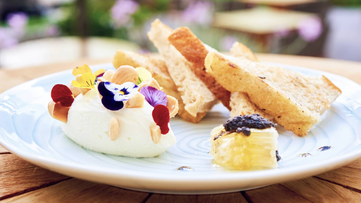 Whipped ricotta on plate with edible flower garnish, honeycomb, toast