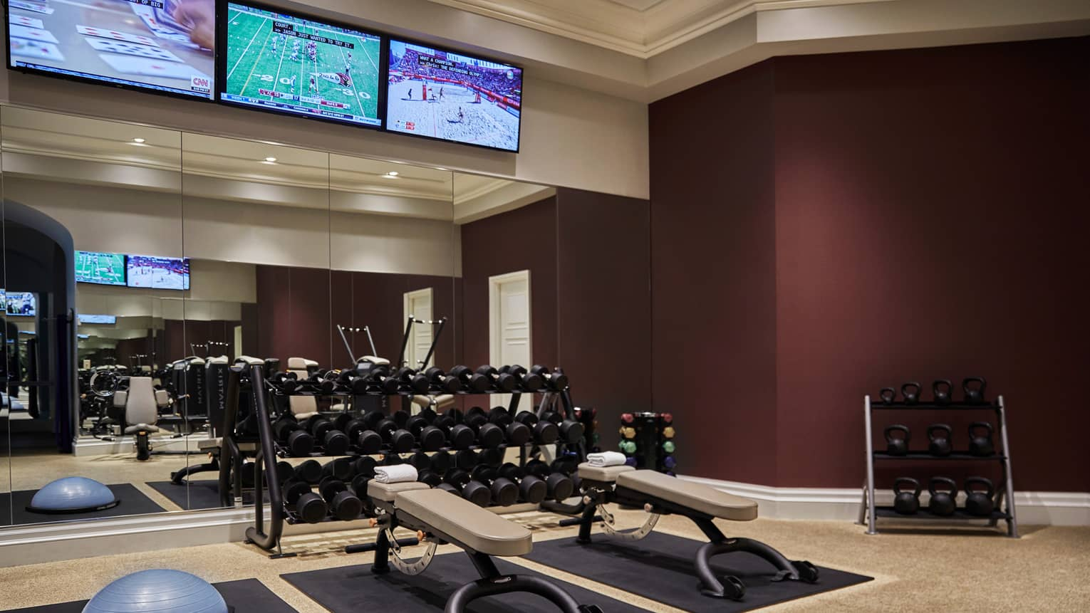 Racks of hand weights, kettlebells by Fitness Centre mirror wall under TVs