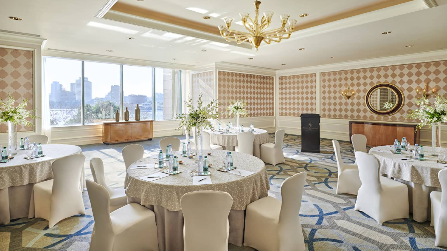 Round banquet tables, linen-covered chairs in sunny Kasr El Nile meeting room