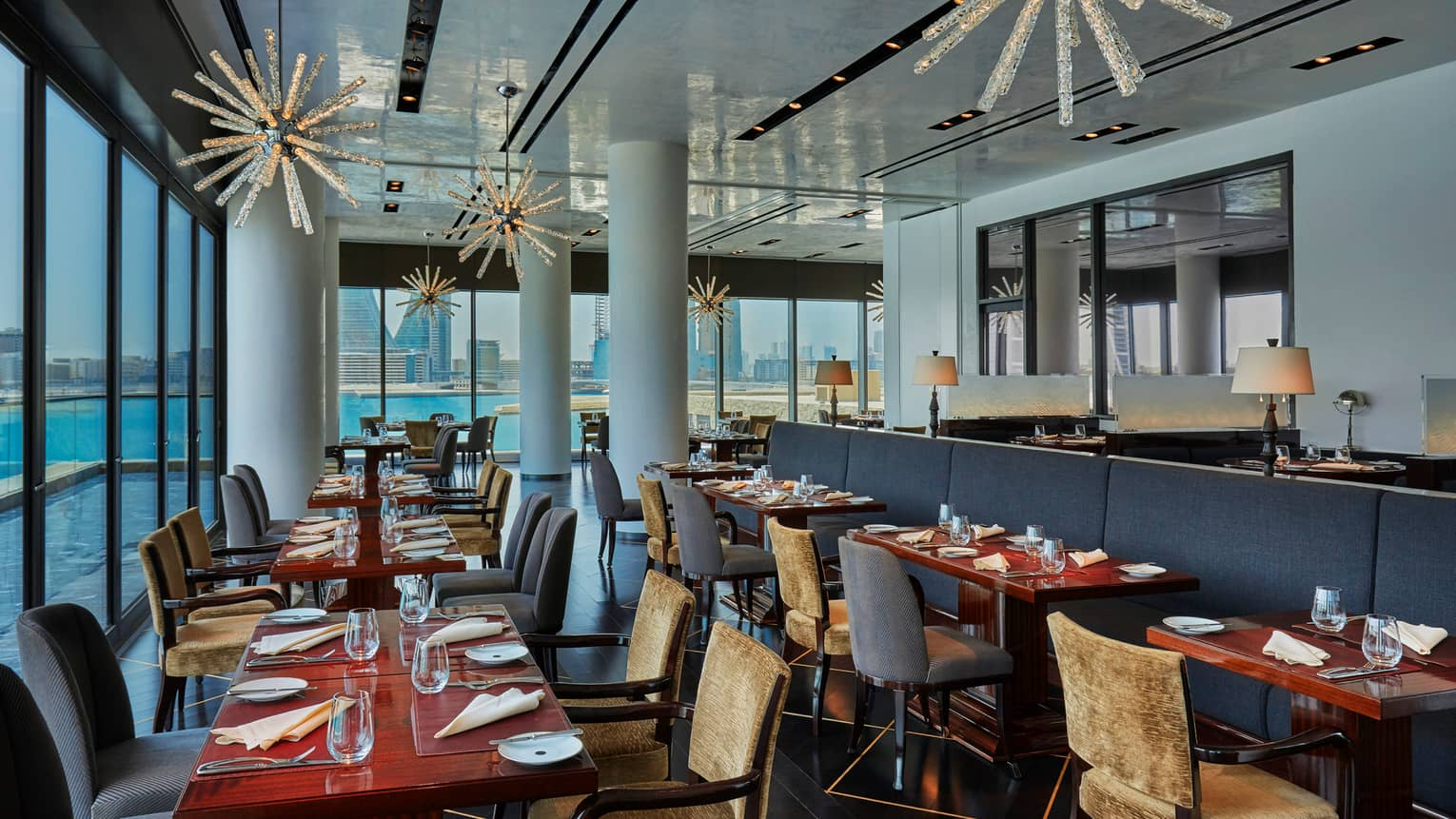 CUT by Wolfgang Puck dining room during day with tables and chairs, white pillars, blue banquette