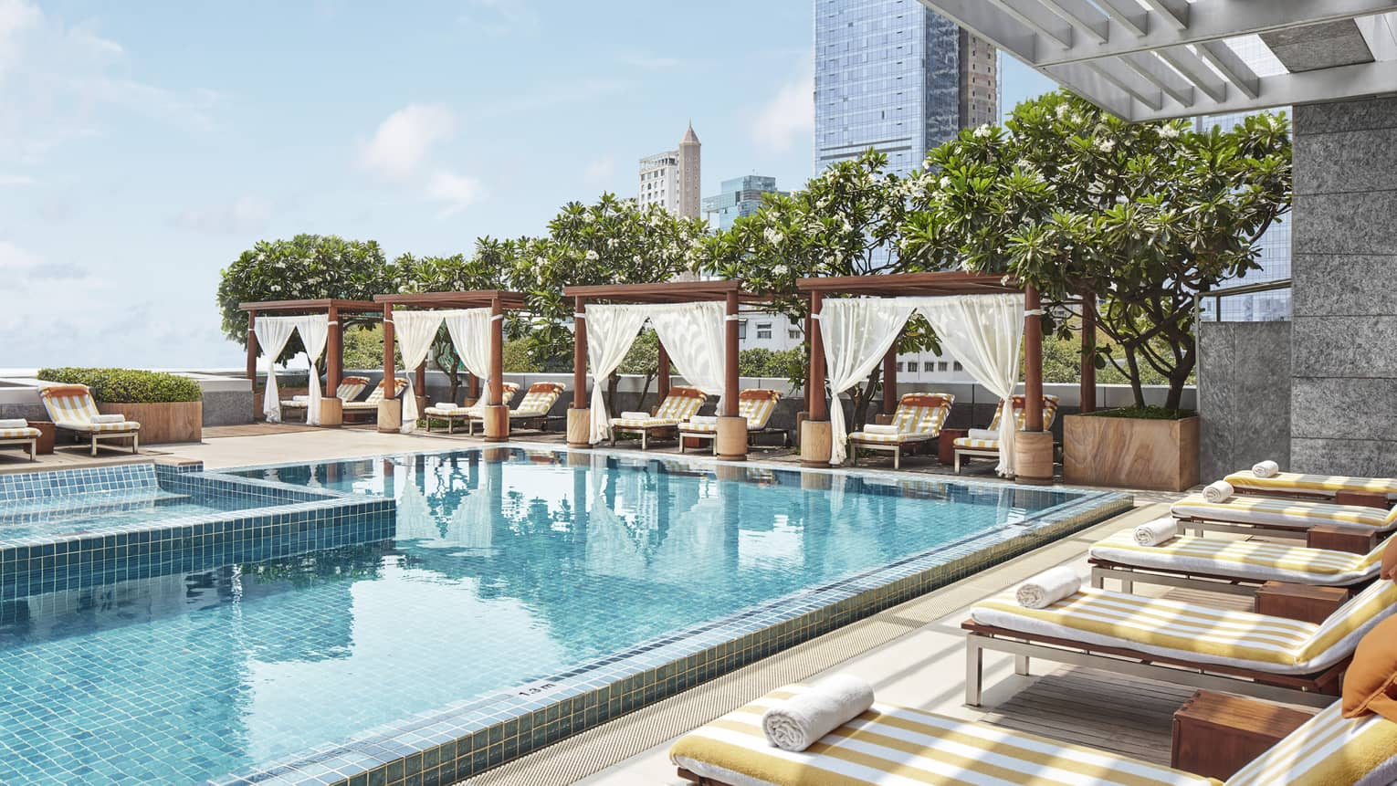 Shaded lounge chairs face the rooftop pool
