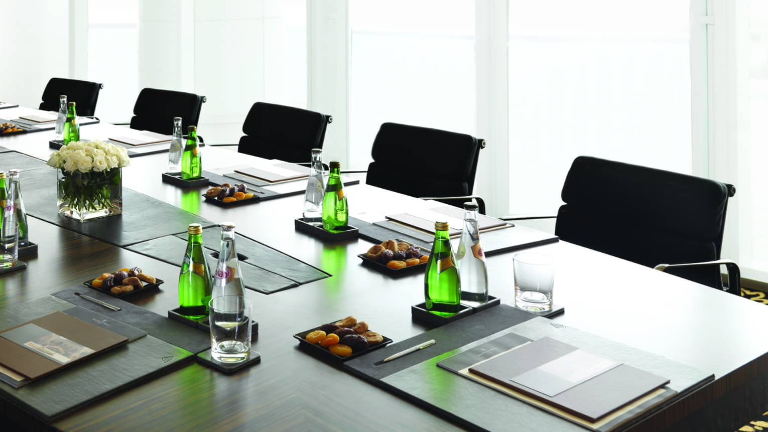 Boardroom meeting table set with water, dried apricots, menus by sunny window