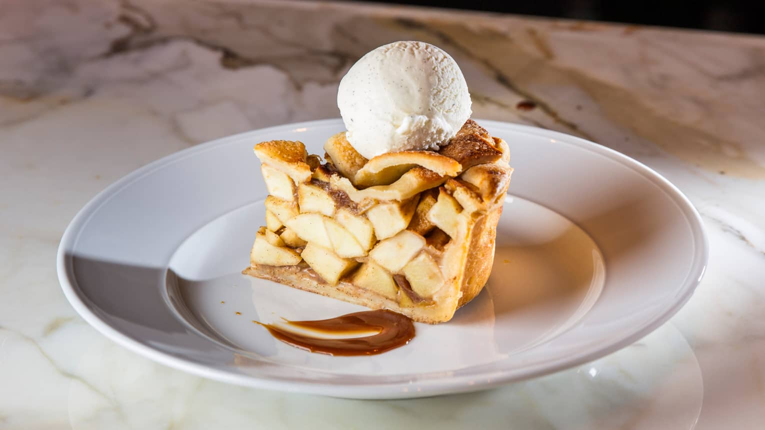 Slice of Double Crusted Apple Pie with large scoop of vanilla ice cream on white plate on white marble counter