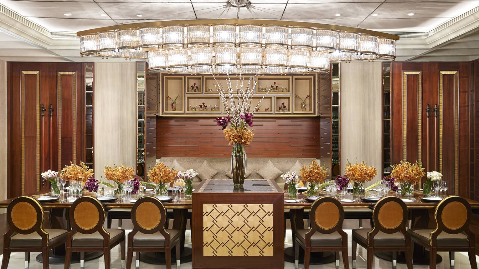 Long private dining table with flower in The Kitchen meeting room with wood walls, crystal lights