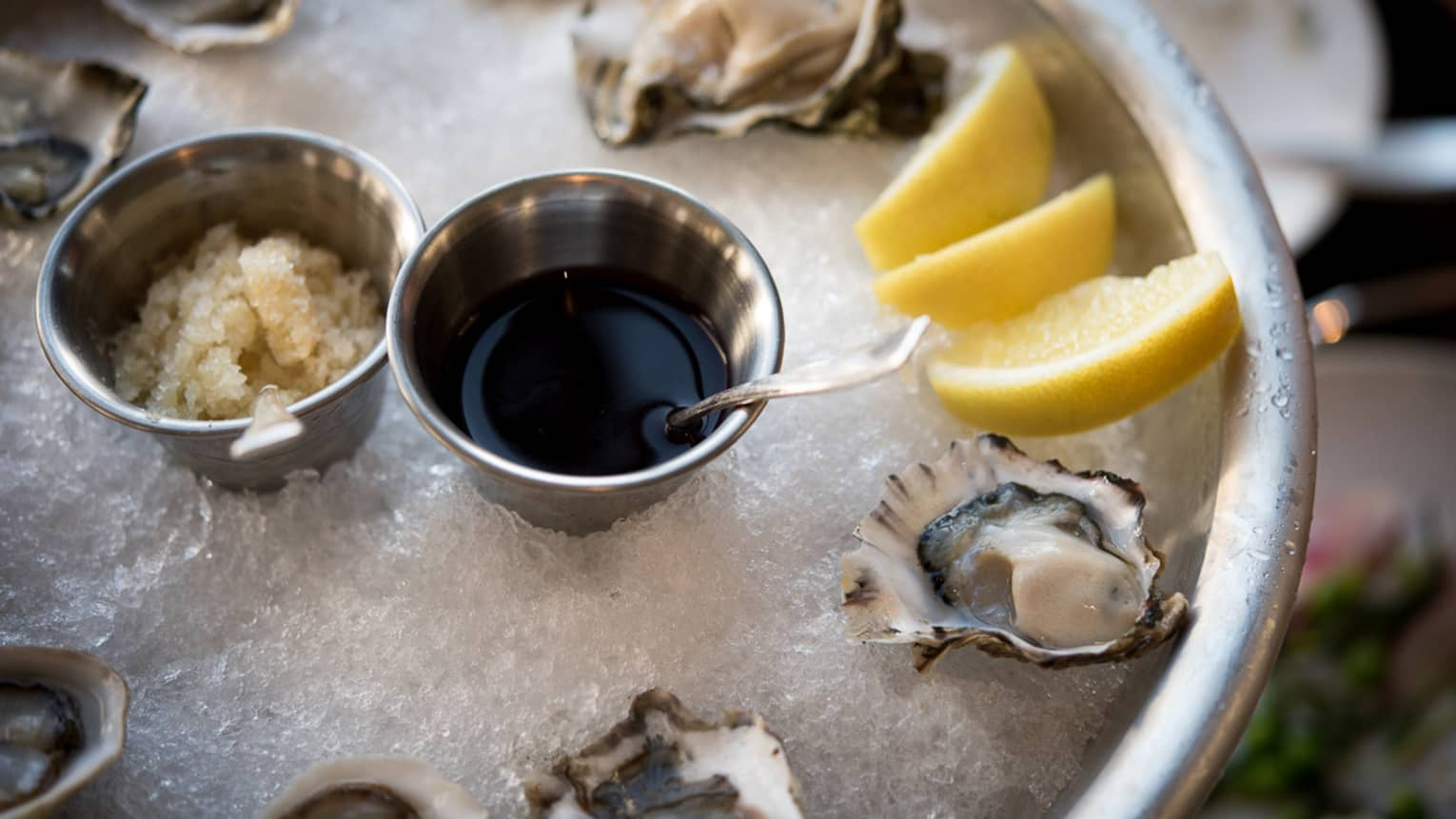 Half-shell oysters, lemon wedges on ice in silver platter
