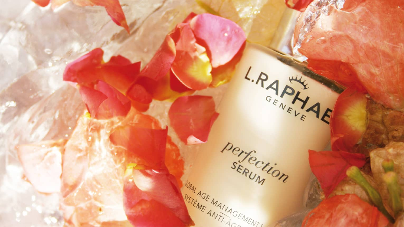 Close-up of bottle of L.RAPHAEL facial serum surrounded by fresh pink flower petals