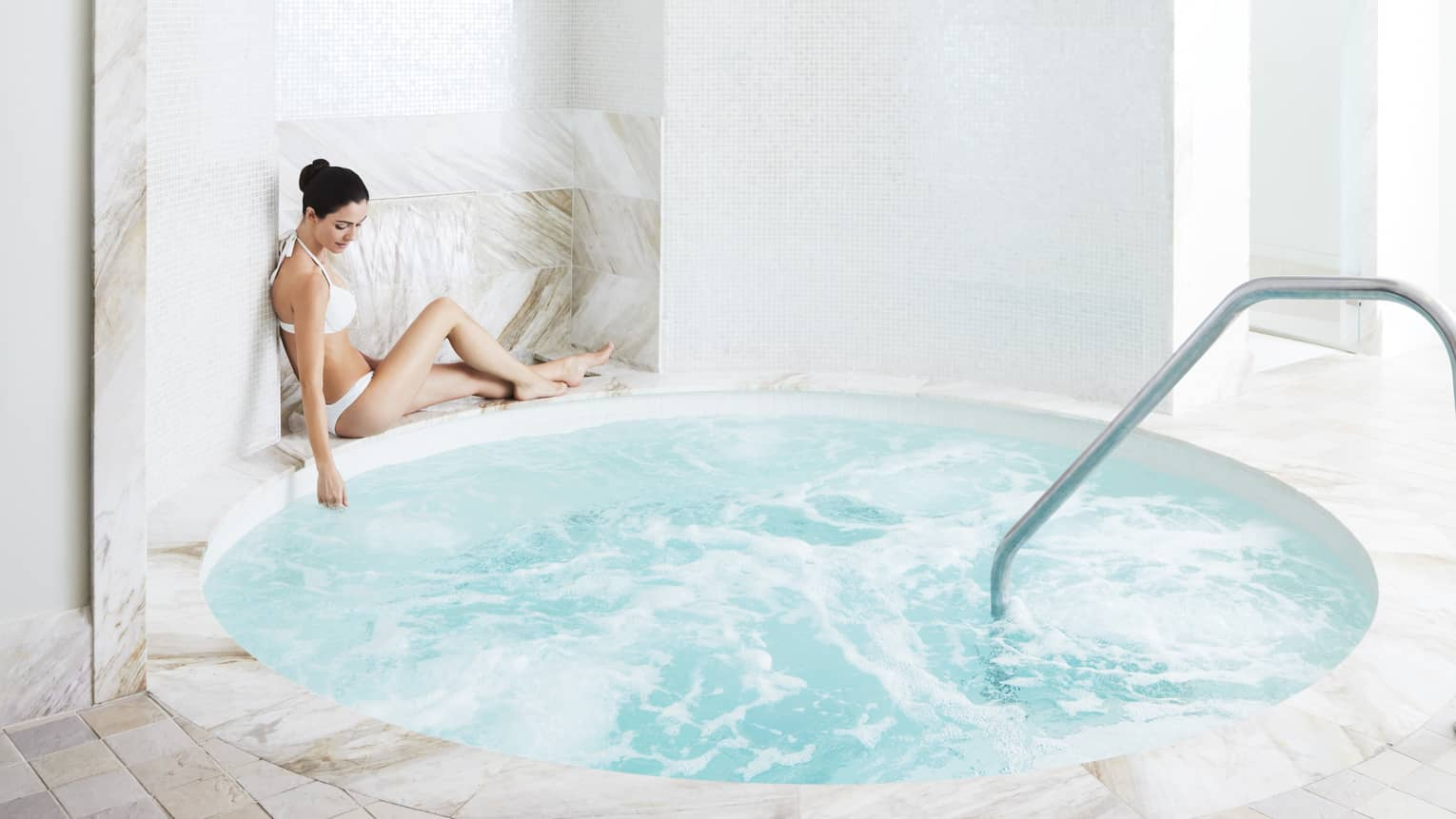 A woman relaxes by a marble hot tub in the spa